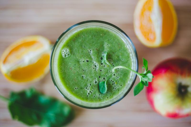 Good morning: Fresh green smoothie and fruits on wooden background, healthy breakfast. Arrangement of a fresh green healthy smoothie and fruits on a wooden royalty free stock photos