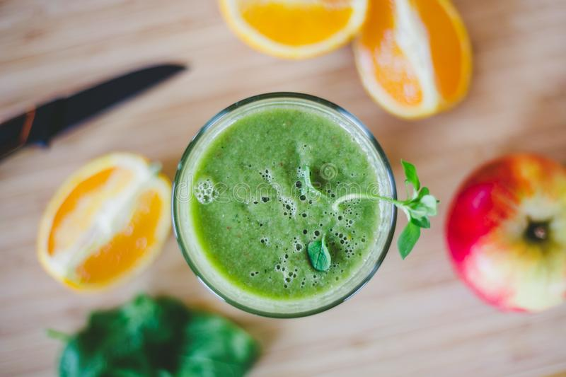 Good morning: Fresh green smoothie and fruits on wooden background, healthy breakfast. Arrangement of a fresh green healthy smoothie and fruits on a wooden stock photo