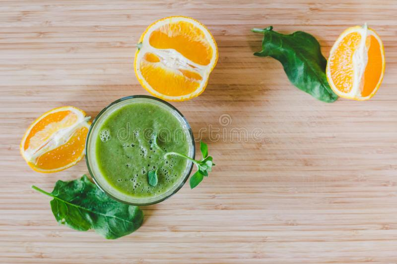Good morning: Fresh green smoothie and fruits on wooden background, healthy breakfast. Text space. Arrangement of a fresh green healthy smoothie and fruits on a stock photo