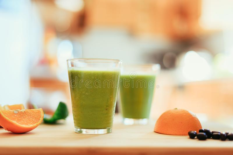 Good morning: Fresh green smoothies and fruits in the kitchen, healthy breakfast. Arrangement of a fresh green healthy smoothies and fruits in the kitchen stock photography