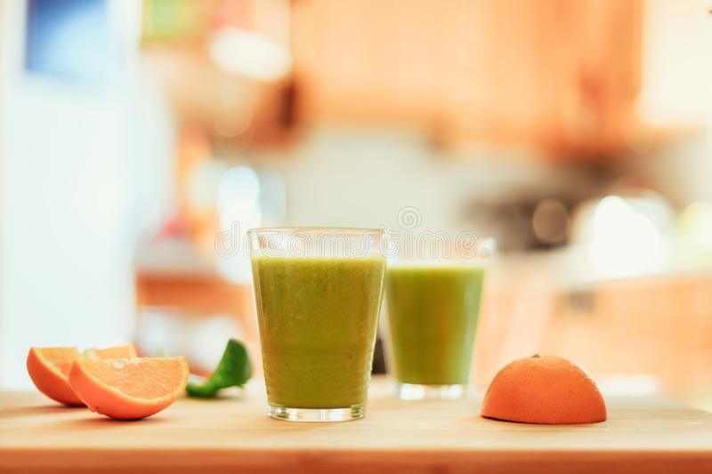 Good morning: Fresh green smoothies and fruits in the kitchen, healthy breakfast. Arrangement of a fresh green healthy smoothies and fruits in the kitchen royalty free stock photos