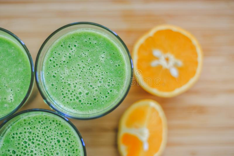 Good morning: Fresh green smoothies and fruits on wooden background, healthy breakfast. Arrangement of a fresh green healthy smoothies and fruits on a wooden royalty free stock photos
