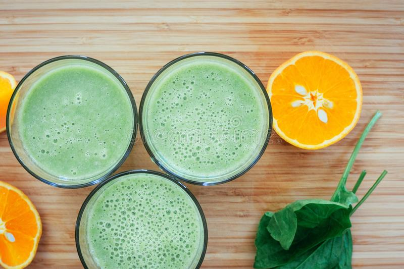 Good morning: Fresh green smoothies and fruits on wooden background, healthy breakfast. Arrangement of a fresh green healthy smoothies and fruits on a wooden stock image
