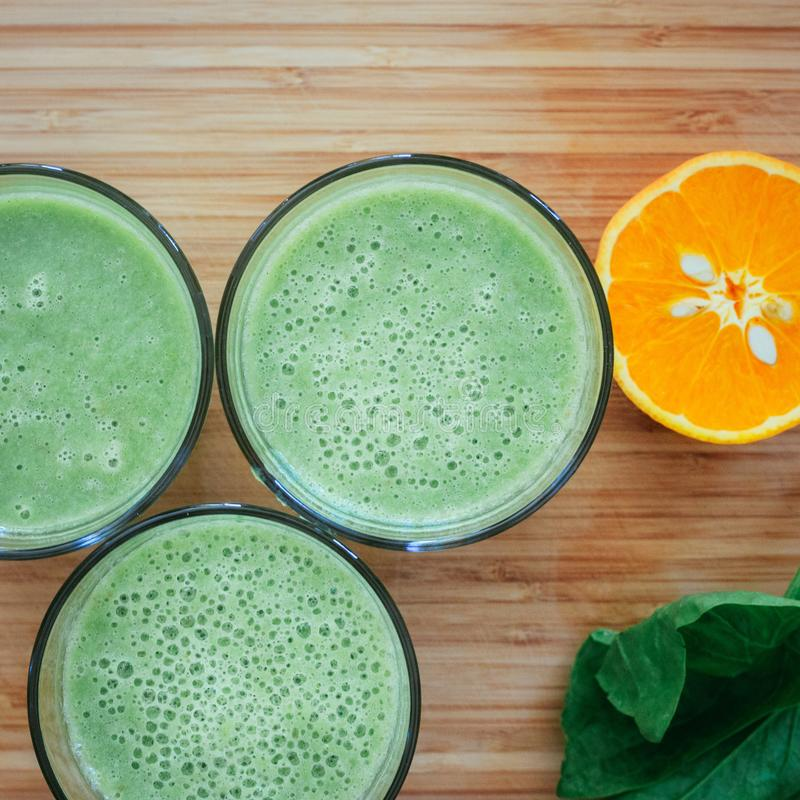 Good morning: Fresh green smoothies and fruits on wooden background, healthy breakfast. Arrangement of a fresh green healthy smoothies and fruits on a wooden royalty free stock photography
