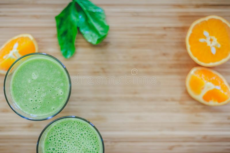 Good morning: Fresh green smoothies and fruits on wooden background, healthy breakfast. Arrangement of a fresh green healthy smoothies and fruits on a wooden royalty free stock image