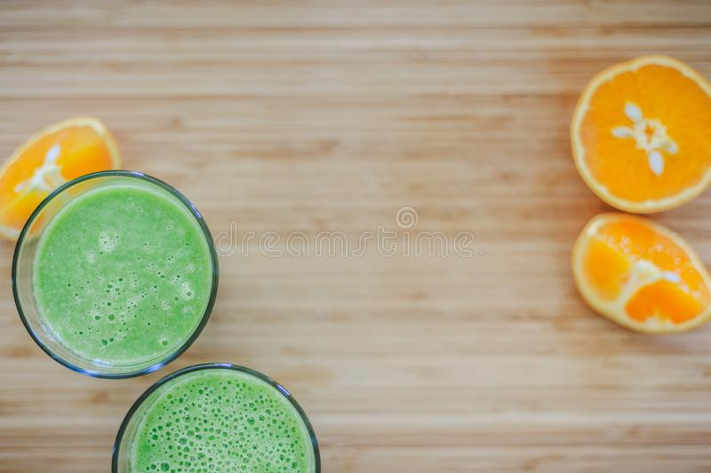 Good morning: Fresh green smoothies and fruits on wooden background, healthy breakfast. Text space. Arrangement of a fresh green healthy smoothies and fruits on royalty free stock photo