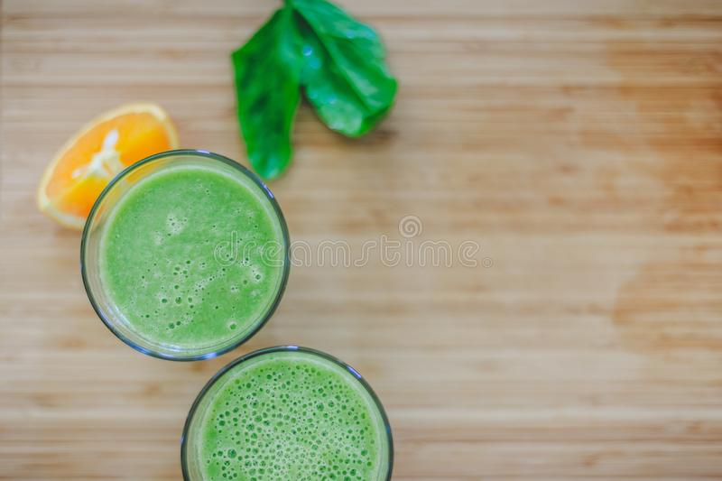 Good morning: Fresh green smoothies and fruits on wooden background, healthy breakfast. Text space. Arrangement of a fresh green healthy smoothies and fruits on stock photos