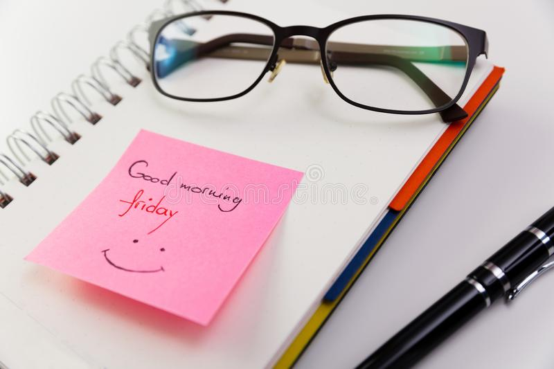 Good morning Friday, written on a post it glued to a notepad wit. H glasses on top royalty free stock image