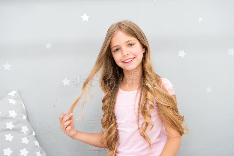 Good morning. Girl child long curly hair awake. Pleasant awakening. Girl looks cheerfully and full of energy in morning. Tips having pleasant morning every day stock photo