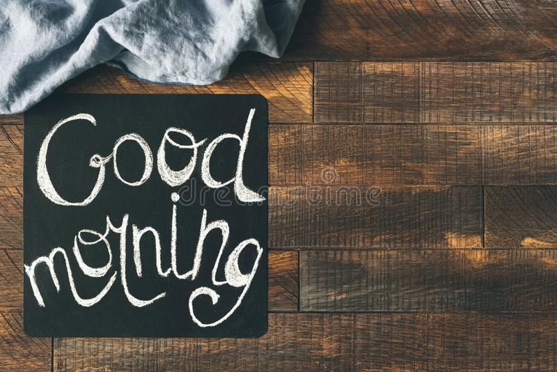 Good morning greeting on blackboard. On a wooden table background. Cheerful morning greeting. Design mock up stock image