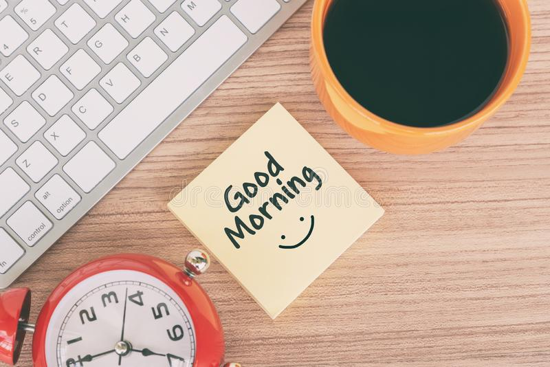 Good morning greeting on paper note. With computer keyboard, coffee and alarm clock pointing at 7 o`clock royalty free stock photography