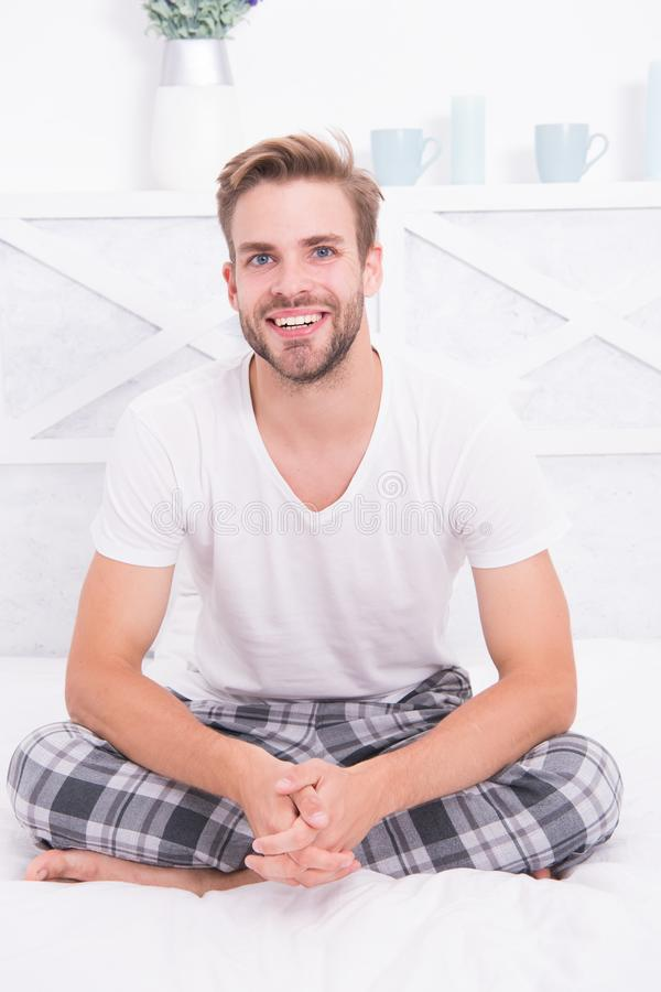 Good morning. Guy happy sit on bed. Man hipster in morning. Asleep and awake. Comfortable relax. Smiling guy wear. Pajamas at home. Cheerful positive energy royalty free stock image
