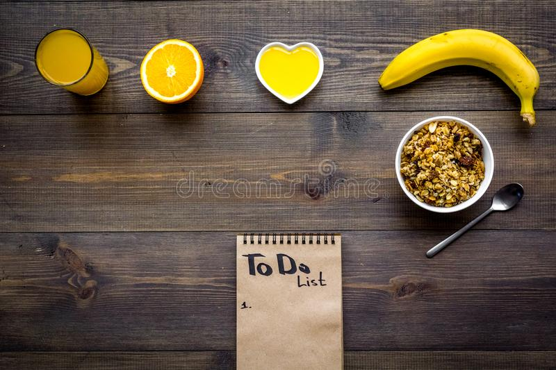 Good morning habits. Eat porridge and fruits and make to do list. Dark wooden background top view copyspace stock photo