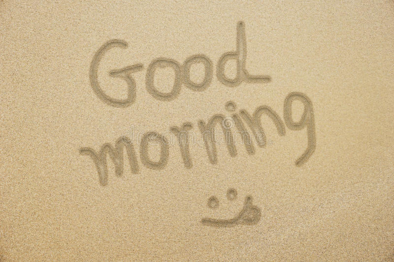 Good morning hand writing with smiling face on samd stock image