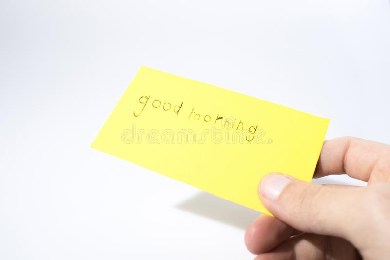 Good morning handwrite with a hand on a yellow paper. Composition stock photo