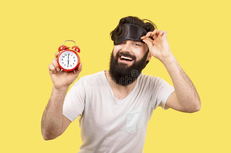 Good morning. Happy bearded man with sleep mask and alarm clock on yellow background, concept good morning stock image