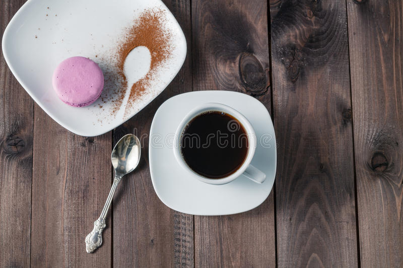 Good morning or Have a nice day message concept - white cup of e. Spresso coffee with colourful French macaron on dark rustic wooden background royalty free stock image