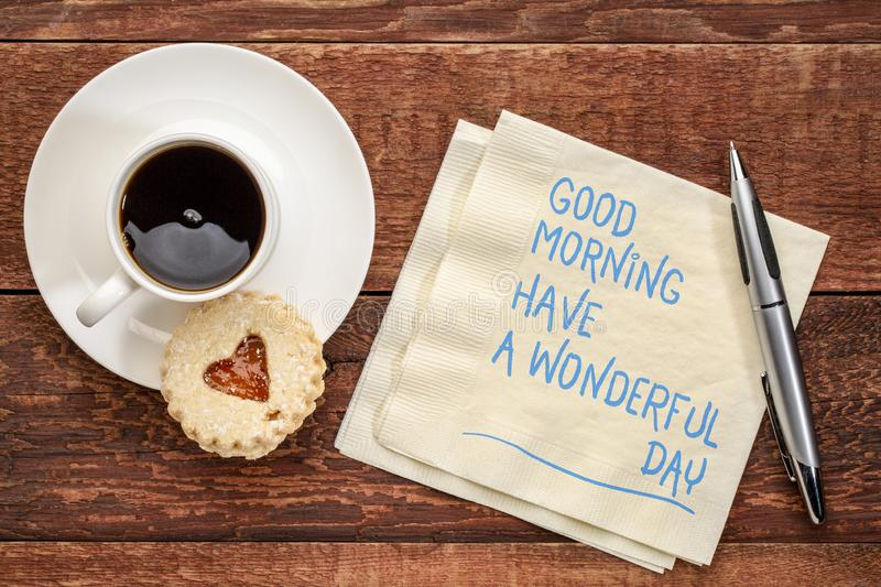 Good Morning, have a wonderful day. Handwriting on a napkin with a cup of coffee and cookie royalty free stock image