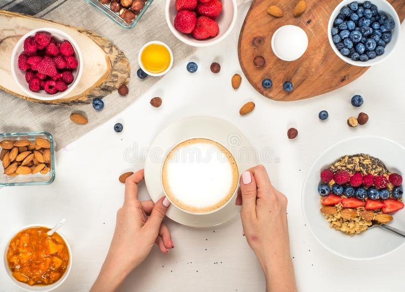 Good morning - healthy breakfast background with oatmeal coffee, berries, egg, nuts. Coffee, hands, hold, cup. White wooden food b royalty free stock photography