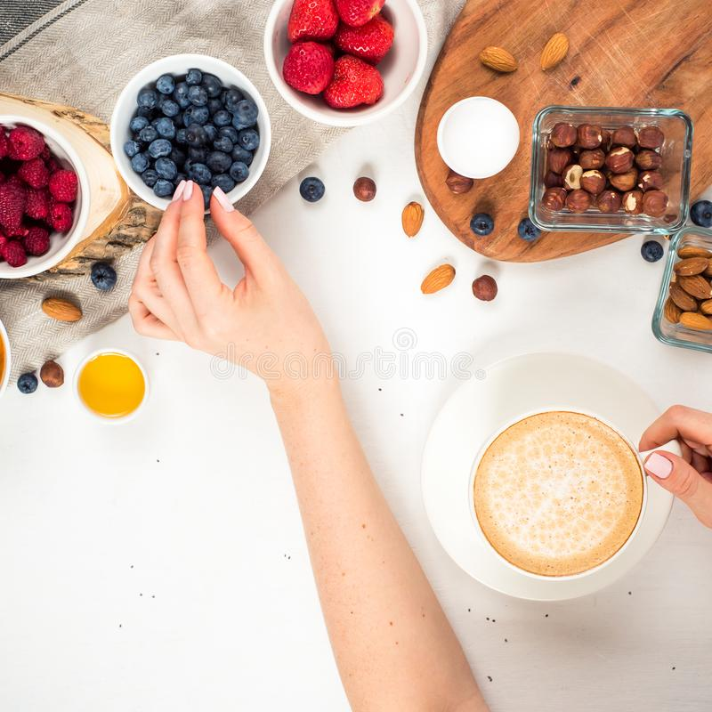 Good morning - healthy breakfast background with oatmeal coffee, berries, egg, nuts. Coffee, hands, hold, cup. White wooden food b stock image