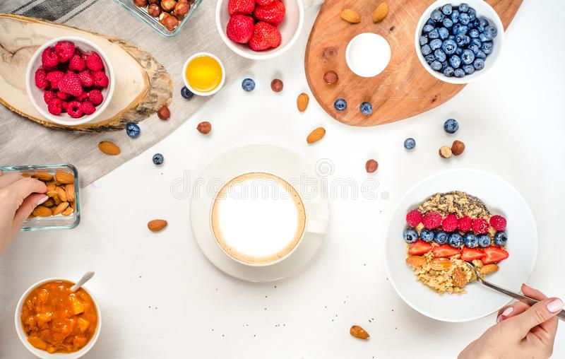 Good morning - healthy breakfast background with oatmeal coffee, berries, egg, nuts. Coffee, hands, hold, cup. White wooden food b royalty free stock photos