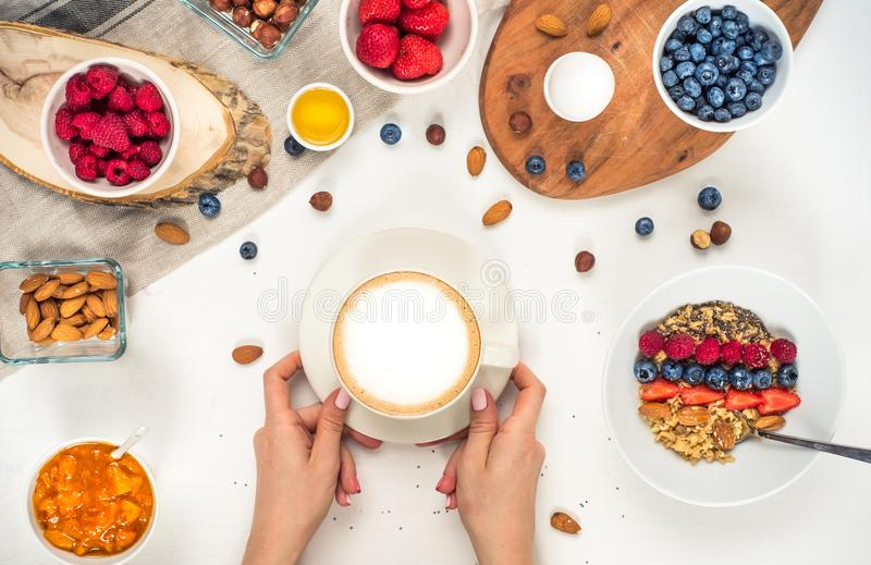 Good morning - healthy breakfast background with oatmeal coffee, berries, egg, nuts. Coffee, hands, hold, cup. White wooden food b. Ackground stock image