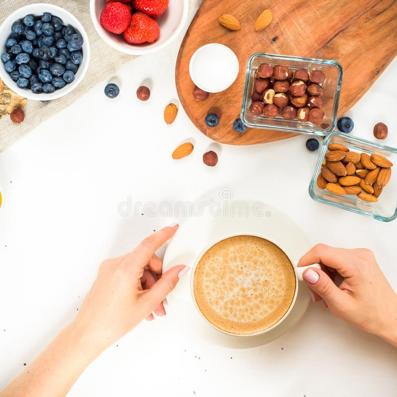 Good morning - healthy breakfast background with oatmeal coffee, berries, egg, nuts. Coffee, hands, hold, cup. White wooden food b. Good morning - granola with royalty free stock images