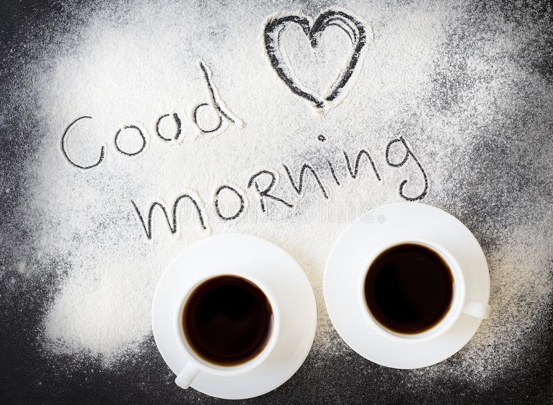 Good morning inscription on the board with flour and two mugs of coffee.  stock image