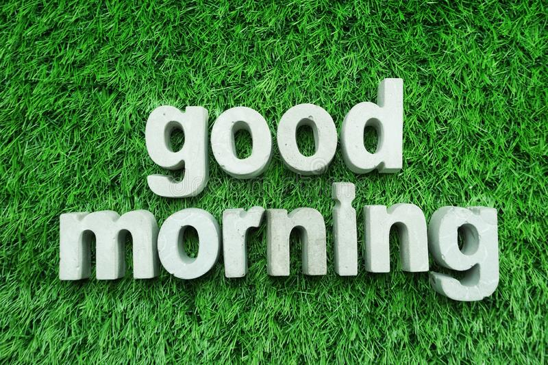 Good Morning made from concrete alphabet on green grass. Good Morning made from concrete alphabet top view on green grass stock image