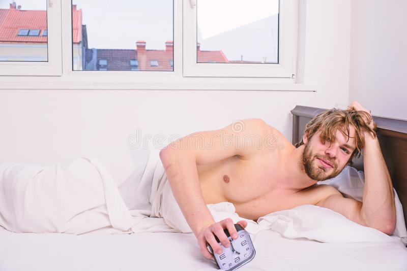 Good morning. Man unshaven lay bed hold alarm clock. Stick schedule same bedtime wake up time. Regulate your bodys clock royalty free stock photography