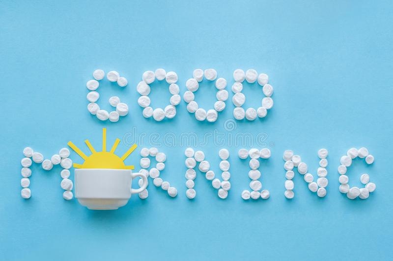 Good morning from marshmallow and coffee cup with rising sun. Co. Text `Good Morning` from marshmallow and coffee cup with yellow rising sun on blue background stock photography