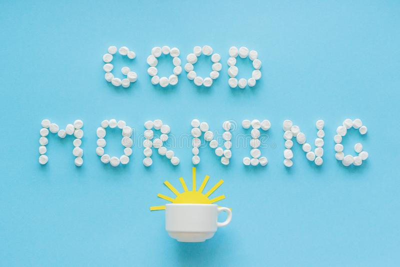 Good morning from marshmallow and coffee cup with rising sun. Text Good Morning from marshmallow and coffee cup with yellow rising sun on blue background royalty free stock photography