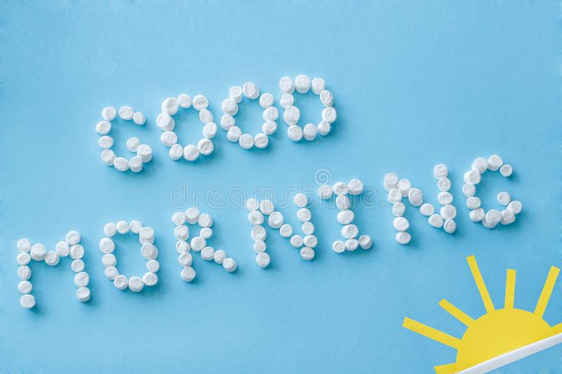 Good morning from marshmallow and figure of rising sun. concept. Text `Good Morning` from marshmallows and figure of rising sun on blue background. Concept royalty free stock photos