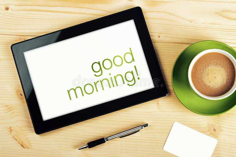 Good Morning Message on Tablet Computer Screen. On Office Table royalty free stock image