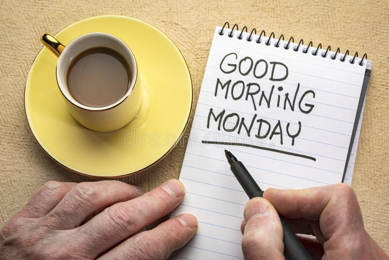 Good Morning Monday note. Good Morning Monday - man hand writing a note with a black marker in a spiral notebook, overhead view with a cup of coffee stock photo