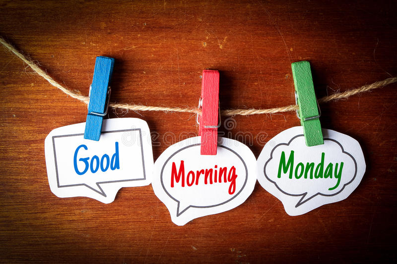Good Morning Monday. Paper speech bubbles with text Good Morning Monday hanging on the line against dark wooden background stock photography