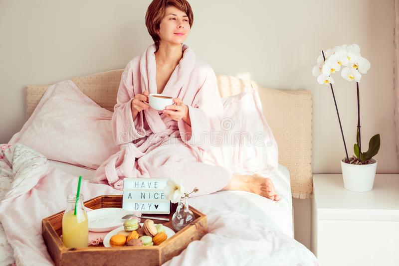 Good morning mood. Young woman in bathrobe sitting on the bed, drinking coffee and has her breakfast in bed with Have a nice day stock photo