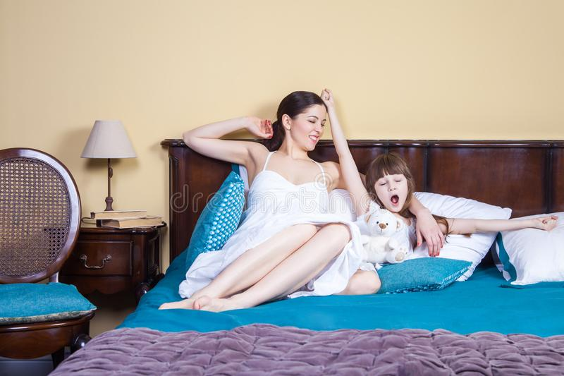 Good morning new day! Mom and child wake up, hands up, stretching and enjoy. Studio shot royalty free stock photography