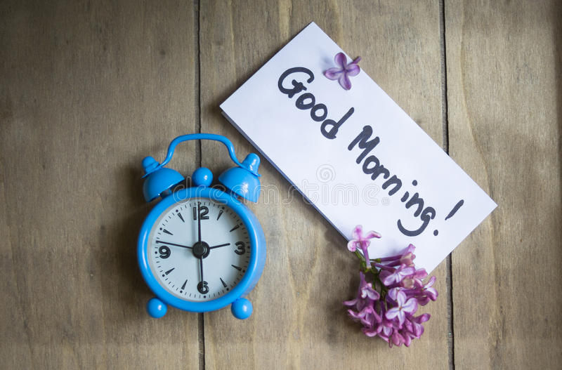 Good morning note and old-styled clock. Good morning note, lilac flowers and old-styled clock on the wooden table royalty free stock photo