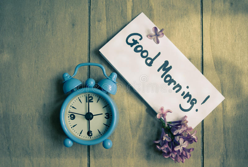 Good morning note and old-styled clock. Good morning note, lilac flowers and old-styled clock on the wooden table stock photography