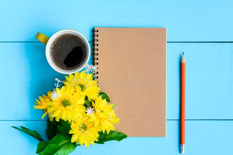 Good morning notebook and coffee. Top view coffee cup and notebook on blue wooden table nature background the good morning .decorate flower stock photos