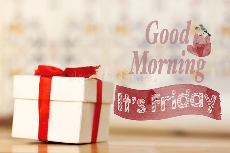 Good morning it`s friday message with white gift box with red ribbon on wood background stock photo