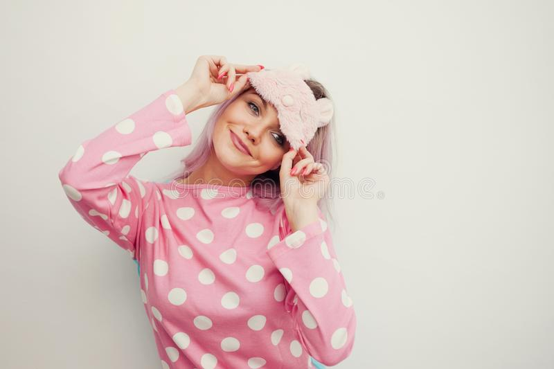 Good Morning. Smiling young woman. Girl in pink pajamas and sleep mask. On white background stock photography