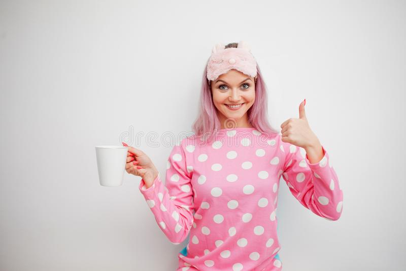 Good Morning. Smiling young woman shows thumb up and drinks coffee. Girl in pink pajamas and sleep mask. On white background royalty free stock image