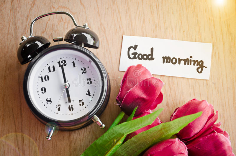 Good morning tag and alarm clock. Good morning tag and alarm clock with red tulip on wood table stock photography