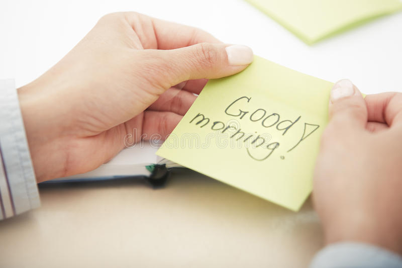 Good morning text on adhesive paper. Hands holding sticky note with Good morning text stock image