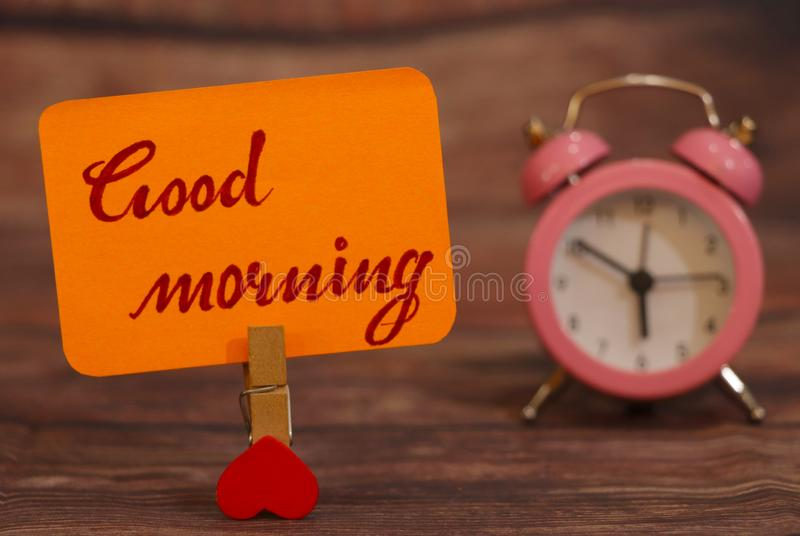 Good Morning text attached with heart clip and alarm clock. royalty free stock photography
