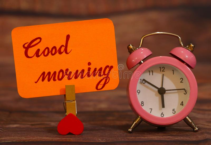 Good Morning text attached with heart clip and alarm clock. stock image