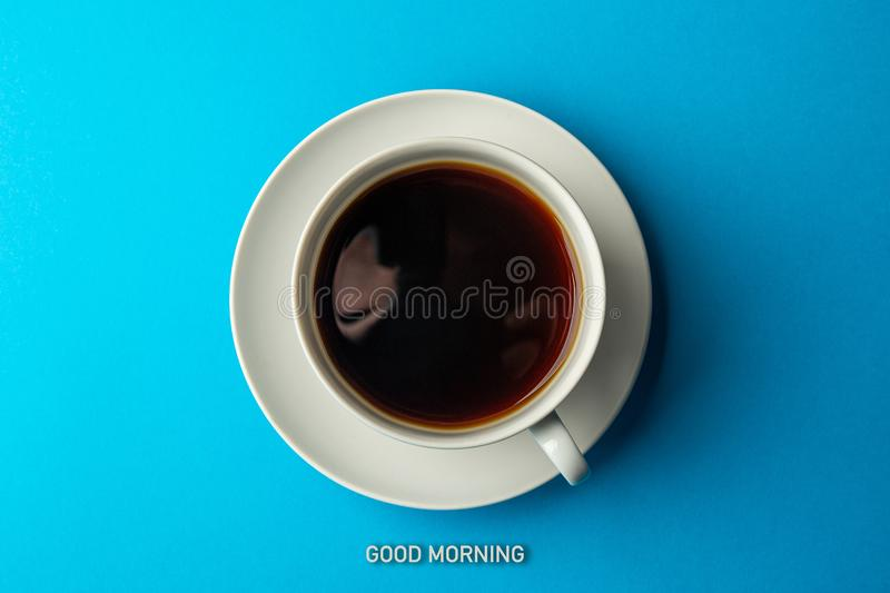 Good Morning - text and cup of coffee on blue background, top view. Minimalism.  stock images