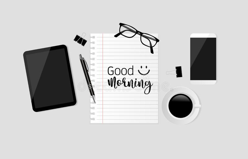 Good morning text on note paper with smartphone, coffee cup, tablet, pen, black paper clips and eyeglasses on gray background. stock photo